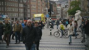 AMSTERDAM, NETHERLANDS - 16 oct 2016, Dam Square - historical center of Holland CAPITAL, tourists, bicycle and cars on. The street, slow motion, wide angle stock video