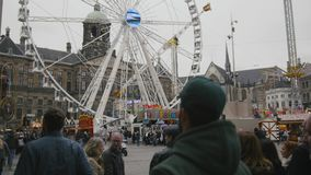 AMSTERDAM, NETHERLANDS - 16 oct 2016, Dam Square - historical center of Holland CAPITAL, tourists, bicycle and cars on. The street, View with amusement Park stock video footage