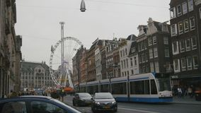 AMSTERDAM, NETHERLANDS - 16 oct 2016, Dam Square - historical ctnter of Holland CAPITAL, tourists, bicycle and cars on. The street, View with amusement Park stock footage