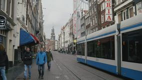 AMSTERDAM, NETHERLANDS - 16 oct 2016, tourists on the street, bicycle and cars - blue tram rides through the historic. Center, wide angle stock video footage