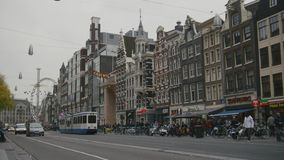 AMSTERDAM, NETHERLANDS - 16 oct 2016, tourists on the street, bicycle and cars - The tram rides through the historic. Center, wide angle stock footage