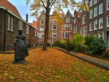Amsterdam / The Netherlands - October 30 2016: Old yard Begijnhof with houses, garden and a sculpture stock image