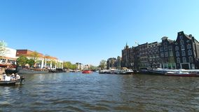 Amsterdam, Netherlands. 25.04.2019. Old ships parked in the canals of Amsterdam. View from the tour boat. Shot with a stock video footage