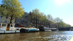 Amsterdam, Netherlands. 25.04.2019. Old ships parked in the canals of Amsterdam. View from the tour boat. Shot with a stock footage