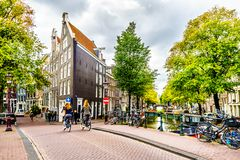 Locals biking over a canal bridge in the Jordaan neighborhood of Amsterdam. Amsterdam, the Netherlands - Sept 28, 2018: Locals biking over a bridge at the royalty free stock images