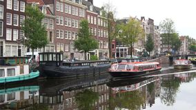 Excursion boats go to the city channel, cloudy september day. Amsterdam. AMSTERDAM, NETHERLANDS - SEPTEMBER 30, 2017: Excursion boats go to the city channel stock video footage