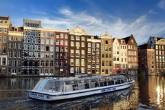 AMSTERDAM, NETHERLANDS - SEPTEMBER 17, 2018: Amsterdam`s famous dancing houses and river boat in the foreground on sunny summer stock photo