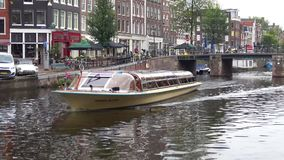 Tour boat on the city canal a gloomy september day. Amsterdam. AMSTERDAM, NETHERLANDS - SEPTEMBER 30, 2017: Tour boat on the city canal a gloomy september day stock footage