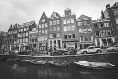Amsterdam, Netherlands: Typical street of old Amsterdam center with cars parked near traditional houses and boats in canal Royalty Free Stock Images