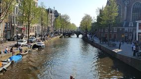 Amsterdam, Netherlands. 25.04.2019. View of Canal in Amsterdam. Tourists walk on a tourist boat on a Sunny day stock video