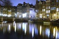 Amsterdam by night. Colorful reflections in a canal in Amsterdam, The Netherlands. This beautiful interplay between the street lighting and the water in the Stock Photos