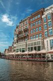 Canal with brick building, restaurant, touristic boat and blue sky in Amsterdam. stock image
