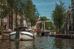 Kayak paddler on tree-lined canal with boat, buildings and blue sky in Amsterdam. Amsterdam, northern Netherlands - June 27, 2017. Kayak paddler on tree-lined Stock Photo