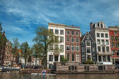 Kayak paddler on tree-lined canal with brick buildings and blue sky in Amsterdam. Amsterdam, northern Netherlands - June 27, 2017. Kayak paddler on tree-lined Stock Photos