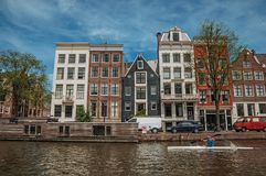 Kayak paddler on tree-lined canal with brick buildings and blue sky in Amsterdam. Amsterdam, northern Netherlands - June 27, 2017. Kayak paddler on tree-lined Stock Photography