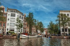 Kayak paddler on tree-lined canal with brick buildings and blue sky in Amsterdam. Amsterdam, northern Netherlands - June 27, 2017. Kayak paddler on tree-lined Stock Images