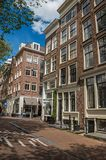 Street with old brick buildings, shops and people passing by in Amsterdam. Amsterdam, northern Netherlands - June 26, 2017. Street with old brick buildings Royalty Free Stock Image