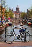 Amsterdam old town canal, boats. Amsterdam, Holland, Netherlands. Church of St Nicholas, old town canal, boats, bike Royalty Free Stock Image