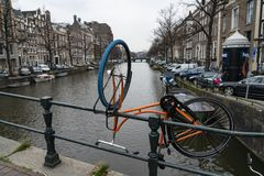 Amsterdam an orange bike upside down along the canals stock photo