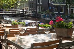 Amsterdam Outdoor Restaurant Dining Tables. Amsterdam restaurant cafe tables set for outdoor dining with glassware and view of canal bridge in the background royalty free stock photography