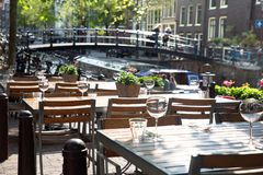 Amsterdam Outdoor Restaurant Dining Tables. Amsterdam restaurant cafe tables set for outdoor dining with glassware and view of canal bridge in the background stock images
