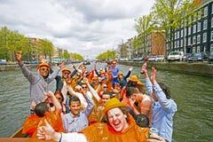 AMSTERDAM, PAÍSES BAJOS - 30 DE ABRIL: Gente en el thr que cruza anaranjado Fotografía de archivo