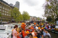 AMSTERDAM, PAÍSES BAJOS - 30 DE ABRIL: Gente en el thr que cruza anaranjado Imagenes de archivo