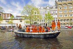 AMSTERDAM, PAÍSES BAJOS - 30 DE ABRIL: Gente en el thr que cruza anaranjado Fotos de archivo libres de regalías