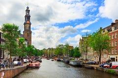 Amsterdam, Países Bajos - 3 de agosto de 2017: Casas de Holanda, iglesia de Westerkerk, barcos y gente tradicionales en el canal  fotografía de archivo libre de regalías