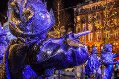 AMSTERDAM, PAÍSES BAJOS - 19 DE DICIEMBRE DE 2015: Las figuras de bronce de soldados en el cuadrado central de la ciudad se encen Foto de archivo libre de regalías