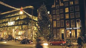 AMSTERDAM, PAÍSES BAJOS - 28 DE DICIEMBRE DE 2017 El árbol de navidad adornado grande y la noche trafican en la calle del comanda Fotos de archivo