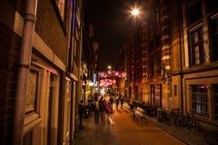 AMSTERDAM, PAÍSES BAJOS - 20 DE ENERO DE 2016: Calles de la noche de Amsterdam con las siluetas borrosas de transeúntes el 20 de  Foto de archivo libre de regalías