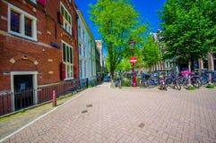 Amsterdam, Países Bajos - 10 de julio de 2015: Calle encantadora típica de la superficie de Bridgestone, edificios holandeses tra Imagen de archivo libre de regalías