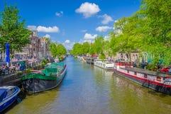 Amsterdam, Países Bajos - 10 de julio de 2015: Canal de agua visto del pequeño puente, de árboles verdes y de edificios residenci Foto de archivo libre de regalías
