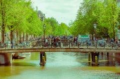 Amsterdam, Países Bajos - 10 de julio de 2015: Dos tiende un puente sobre estiramientos sobre el canal de agua y hords de la gent Foto de archivo