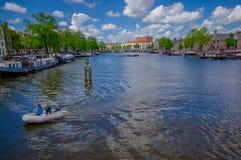 Amsterdam, Países Bajos - 10 de julio de 2015: El canal de agua grande que corría a través de ciudad con varios barcos parqueó al Fotos de archivo