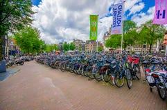 Amsterdam, Países Bajos - 10 de julio de 2015: Estacionamiento enorme de la bicicleta en el centro de ciudad, probando que los ho Imagen de archivo