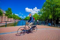 Amsterdam, Países Bajos - 10 de julio de 2015: Hombre holandés típico que monta en bicicleta sobre un puente del canal, en su man Imagenes de archivo