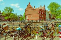 Amsterdam, Países Bajos - 10 de julio de 2015: Monte en bicicleta parquear junto a uno de los muchos canales de agua que corren a Imagen de archivo