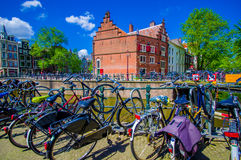 Amsterdam, Países Bajos - 10 de julio de 2015: Monte en bicicleta parquear junto a uno de los muchos canales de agua que corren a Imágenes de archivo libres de regalías