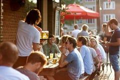 Amsterdam, Países Bajos 19 de julio de 2017 Gente joven que cuelga hacia fuera en café del verano Foto de archivo