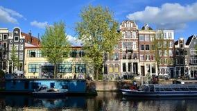 Amsterdam, Países Bajos - 7 de mayo de 2015: Casas tradicionales de Amsterdam con el canal en Amsterdam almacen de metraje de vídeo