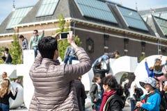 Amsterdam, Paesi Bassi - 31 aprile 2017: Equipaggi la presa dei selfies mentre la gente che cammina intorno nelle vie Fotografia Stock Libera da Diritti