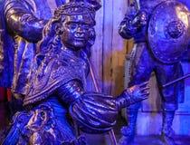 AMSTERDAM, PAESI BASSI - 19 DICEMBRE 2015: Le figure bronzee dei soldati sul quadrato centrale della città si sono accese con ilu Fotografia Stock Libera da Diritti