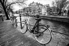 Amsterdam, Paesi Bassi - 26 febbraio 2010: Bicicletta sulla via vicino al canale dell'acqua Le biciclette sono il trasporto molto fotografie stock