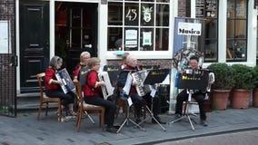 Amsterdam, Paesi Bassi - 14 giugno 2017: Orchestra dei giocatori della fisarmonica su una via pedonale nella vecchia città di Ams stock footage