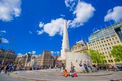 Amsterdam, Paesi Bassi - 10 luglio 2015: Argini il quadrato un bello giorno soleggiato, un monumento alto e le costruzioni storic Fotografie Stock Libere da Diritti