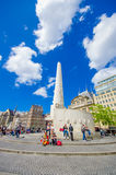 Amsterdam, Paesi Bassi - 10 luglio 2015: Argini il quadrato un bello giorno soleggiato, un monumento alto e le costruzioni storic Fotografia Stock