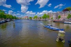 Amsterdam, Paesi Bassi - 10 luglio 2015: Il grande canale idrico che passa la città con parecchie barche ha parcheggiato di fianc Fotografie Stock