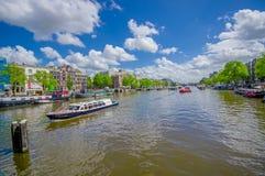 Amsterdam, Paesi Bassi - 10 luglio 2015: Il grande canale idrico che passa la città con parecchie barche ha parcheggiato di fianc Fotografia Stock